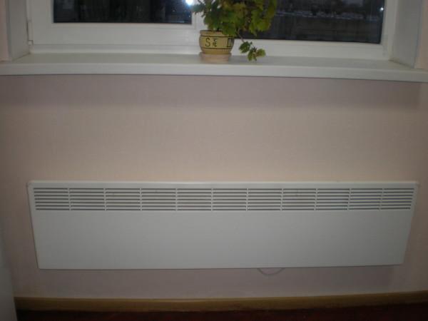 Настенный конвектор создает тепловую завесу перед оконным проемом.