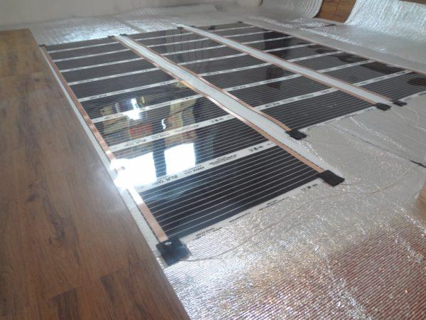 Пленочный нагреватель укладывается прямо под ламинат. Работы могут быть выполнены во время чистовой отделки или после ее завершения.
