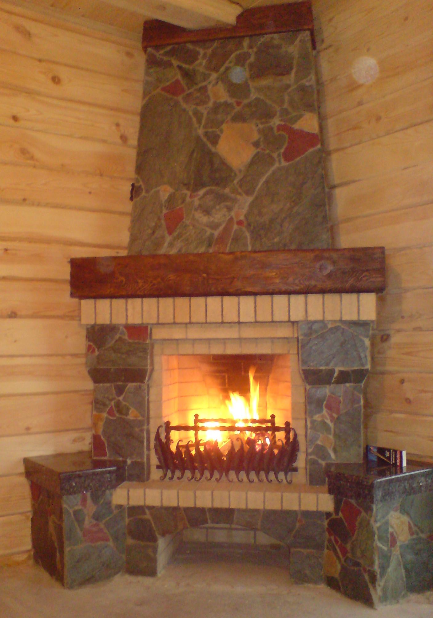 Пример небольшого углового камина в деревянном доме