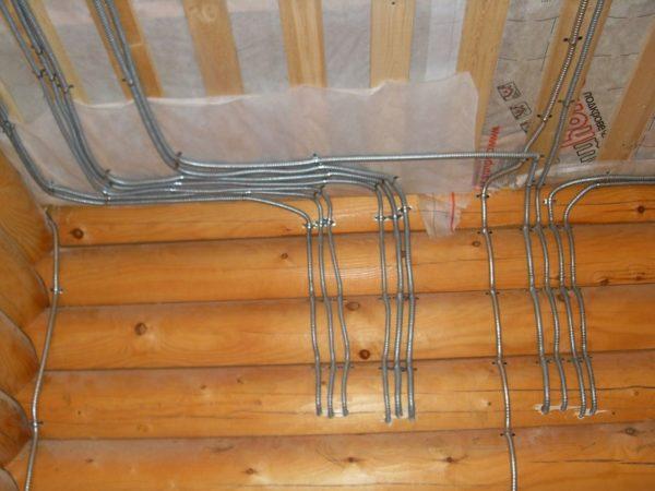 Прокладка проводки в деревянном доме. Провода разводятся в гофрированных металлорукавах.
