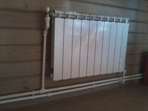 Радиатор на стене и подведенные к нему трубы — характерный признак отопления на жидком теплоносителе