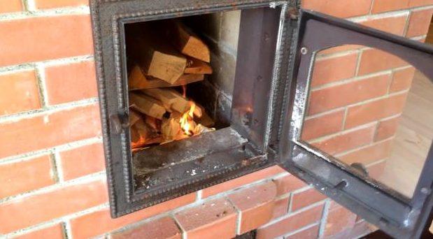 Уложенные в русскую печь дрова смотрят из топливной камеры торцами наружу, соответствуя правилу укладки поперёк решётки