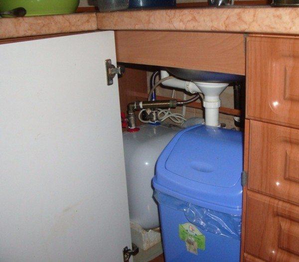 Водонагреватель с верхней подводкой в кухонной тумбе.
