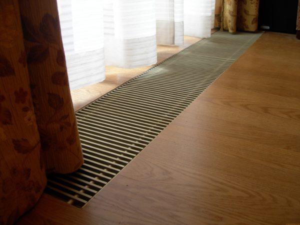 Встраиваемый в пол конвектор наиболее выгодно устанавливать на границе с окнами или дверьми для создания тепловой завесы, защищающей комнату от уличной прохлады или смежных помещений