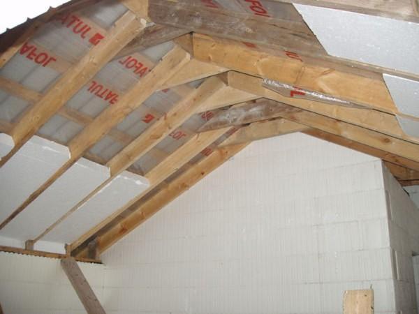 Закладка пенопласта в двускатную деревянную крышу.