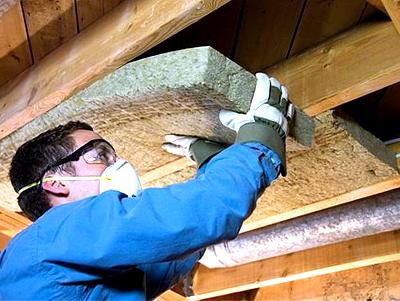 Закладка ватных плит между потолочными направляющими.