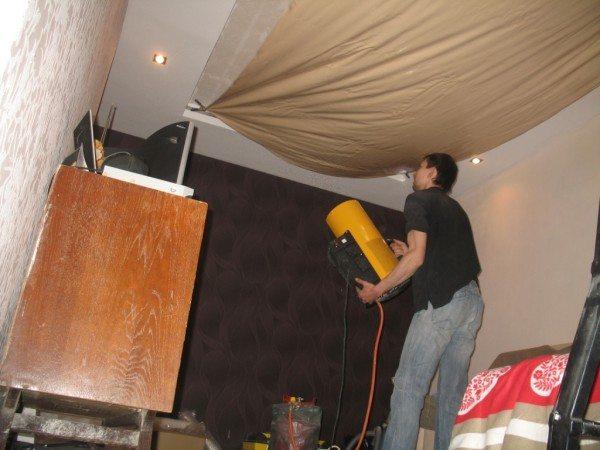 На фото использование газовой пушки для монтажа натяжного потолка.