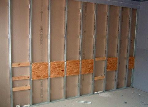 На стены из ГКЛ монтируется усиление – основание из дерева