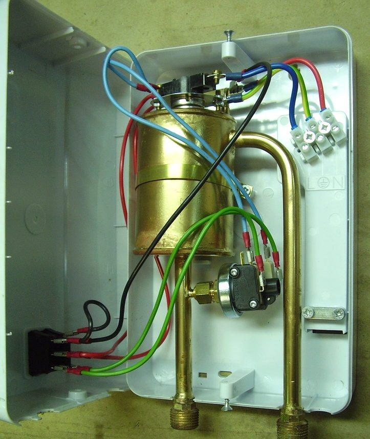 По центру фотографии расположен теплообменный стакан из латуни, а к входному патрубку подключен датчик протока воды.