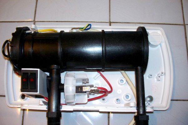 Проточный нагреватель Atmor Basic со снятой лицевой панелью. В его конструкции всего три элемента: бак с ТЭНами, двухклавишный выключатель и реле давления.