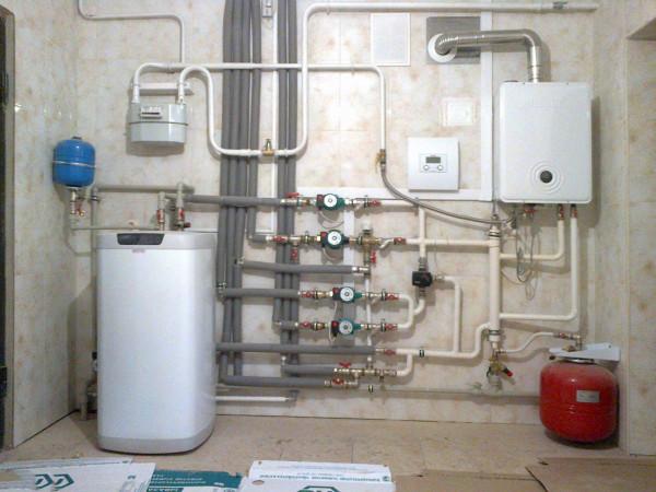 Слева - напольный бойлер косвенного нагрева, справа - настенный газовый котел.