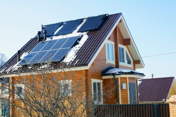 Вакуумные коллекторы отопления и солнечные батареи на крыше частного дома.